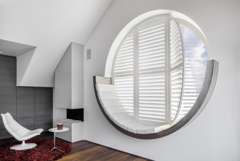 round window with white wooden shutters with white chair