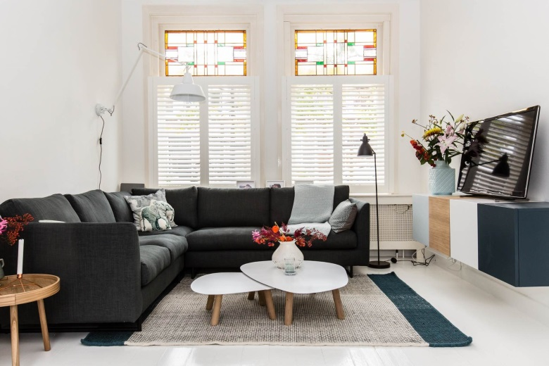 white wooden shutters in living room with stained glass window